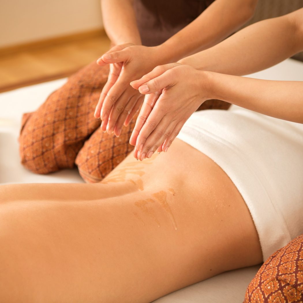 Young woman in Thai SPA enjoying back massage.