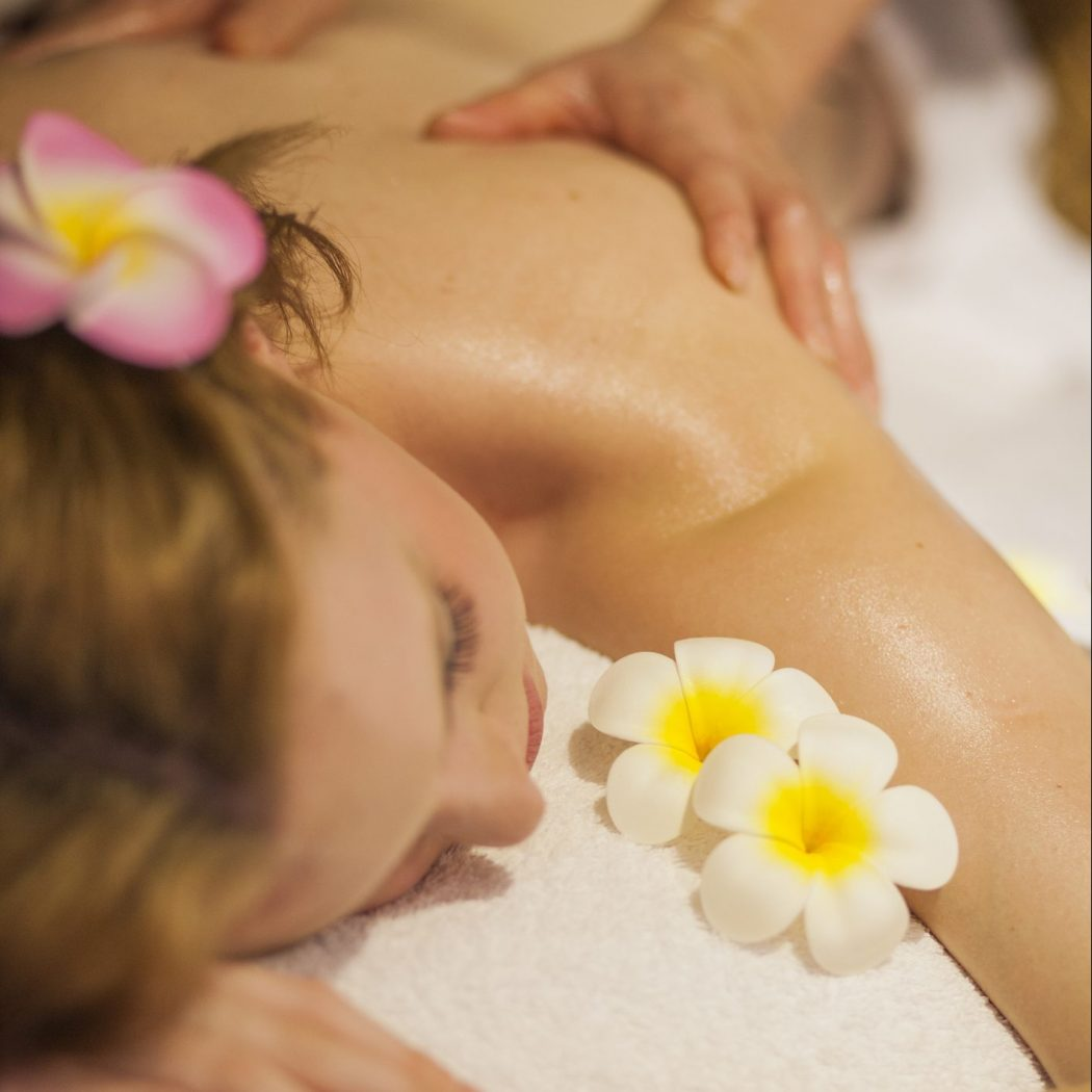 Young female getting massage in Thai massage salon. With some flowers and aromas.